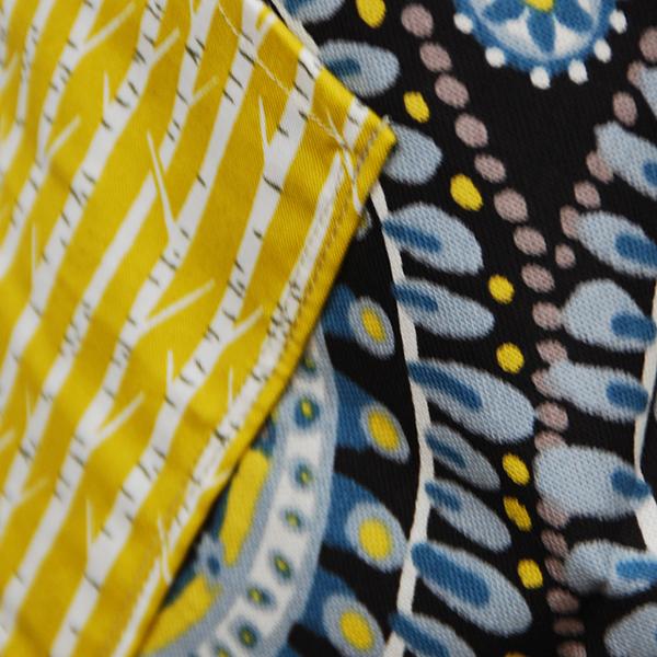 tablier à dos croisé aux beaux motifs bohèmes et poches en tissus à fond jaune.