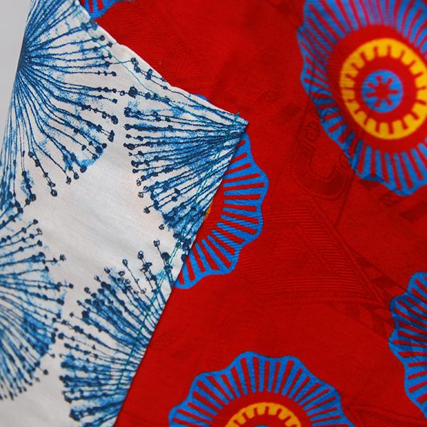 Tablier en belle wax rouge au motifs bleu et orange avec poches à motif bleu sur fond blanc.