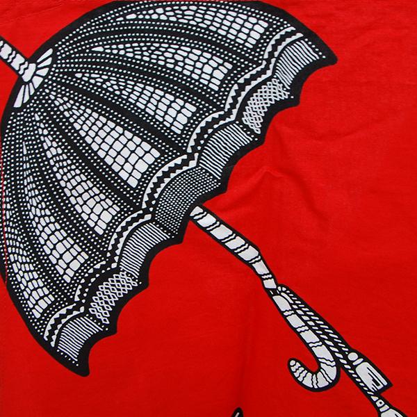 Tablier en wax rouge avec motifs noir et blanc en forme d'ombrelles.