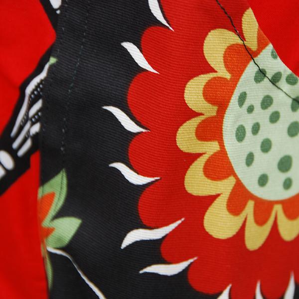 Tablier en très belle wax d'un beau rouge avec motifs 'ombrelles' en noir et blanc avec poches aux motifs floraux sur fond noir.