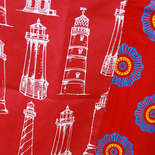 tablier rouge à motifs de phares avec poche en wax rouge à motifs bleus.